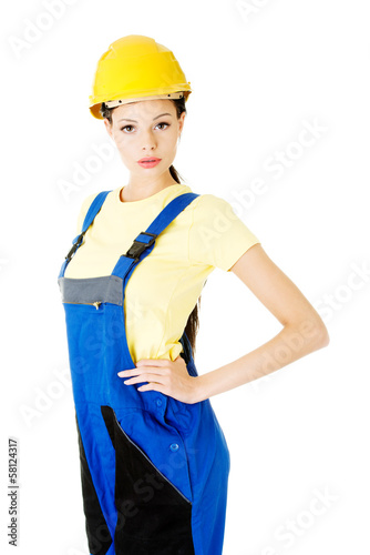Attractive woman wears work clothes and helmet.