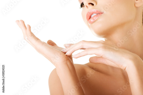Attractive naked woman closeup. View on hands.