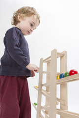 child playing with wooden ball path