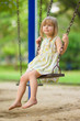 Adorable girl swinging on kids playground