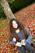 Young Teenage Girl outside reading a book during Autumn Season
