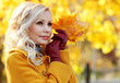 Autumn Girl. Fashion Blonde Beautiful Woman with Maple leaves in