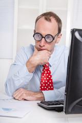Mann sitzt nachdenklich am Schreibtisch im Büro mit Krawatte