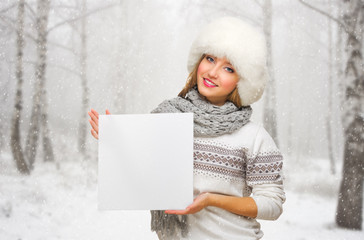 Young girl with blank poster on snowy forest