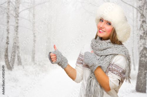 Young girl shows ok gesture on snowy forest
