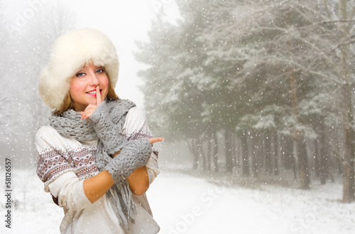 Young girl shows pointing gesture on snowy forest