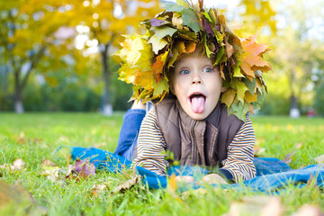 Portrait of cheerful child in a wreath from autumn leaves