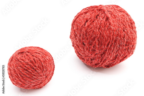 Closeup of small and big red wool ball. White background