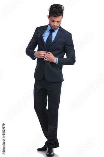 fashion business man un buttoning his suit and looking down