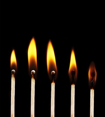set of burning matchsticks on black background
