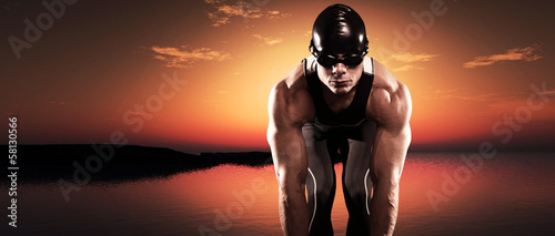 Swimmer muscled triathlon man with cap and glasses outdoor at a