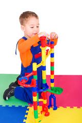 kleiner Junge spielt mit der Murmelbahn