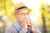 Mature man blowing his nose in tissue because of being ill