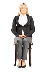 Confident blond businesswoman in suit sitting on a chair