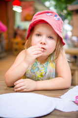 Adorable girl in pink hat eat pizza in street pizzeria