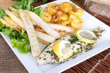gedünsteter Fisch an Bratkartoffeln und weißem Spargel