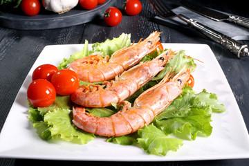 pesce gamberi alla griglia su insalata verde piatto bianco