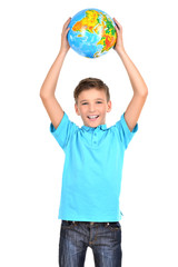 Smiling boy in casual  holding globe in hands above his head