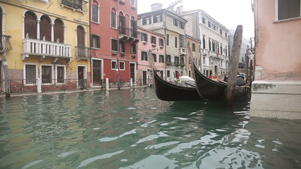 Gondolas in Venice at the pier at the channel