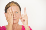 Mature woman testing focus of eyesight