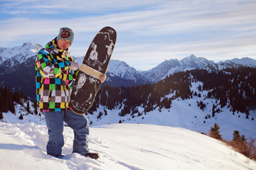 Sport man in snowy mountains at sunset
