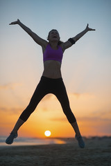 Silhouette of fitness young woman jumping on beach at dusk