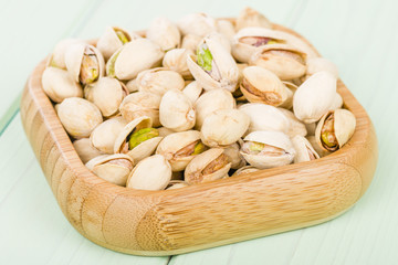 Pistachios - Roasted and salted pistachio nuts in a bamboo bowl