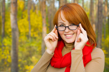 Portrait of beautiful red-haired girl in glasses