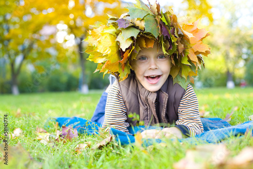 portrait of the cheerful child in a wreath from autumn leaves