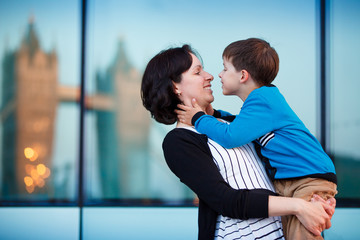 Loving mother and son hugging outdoors in city