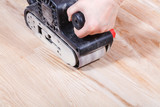 finishing wooden surface by hand-held belt sander poster