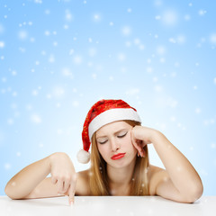 Young woman in santa claus hat posing with wearied look on blue