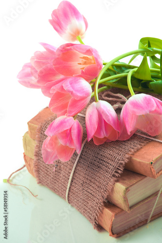 Pink tulips on old books