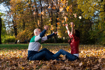 Loving Couple Toss The Leaves In Autumn Park