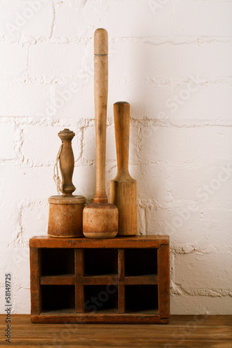 retro kitchen utensils  mashers on old wooden spice box in rusti