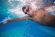 Young man swimming the front crawl in a pool - underwater shot