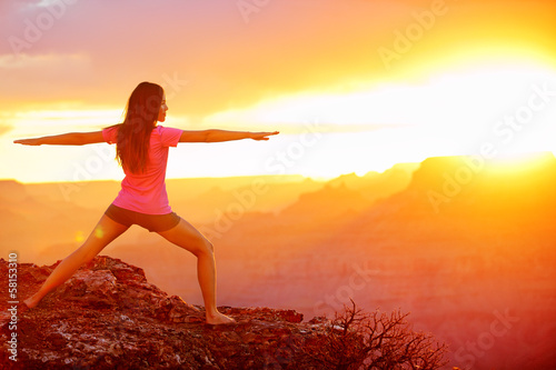 Yoga woman meditating at sunset in Grand Canyon