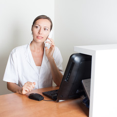 Medical receptionist on phone in front of computer