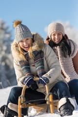 Two female friends sledge downhill in wintertime