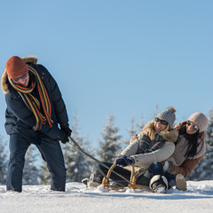 Friends having fun on sledge sunny winter