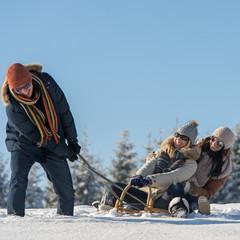 Friends having fun on sledge sunny winter