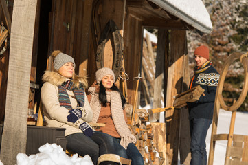 Young people by wooden winter cottage sunny