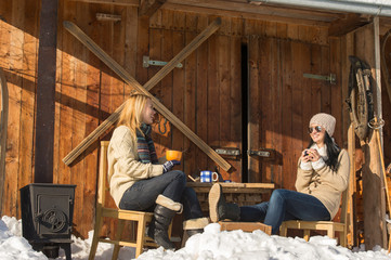 Two girlfriends enjoy tea winter snow cottage