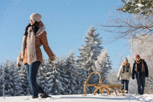 Sunny winter day woman pulling sledge