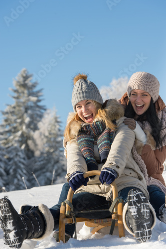 Laughing teenagers sledge downhill in wintertime