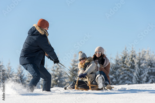Young man pulling girls on winter sledge