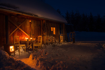 Cozy wooden cottage in dark winter forest