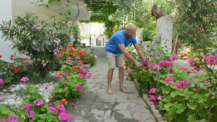Footage of a man pruning some flowers