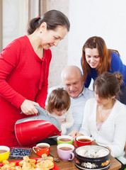 Mature woman pours tea for family