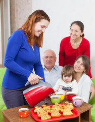 Woman pours tea from teapot for  family